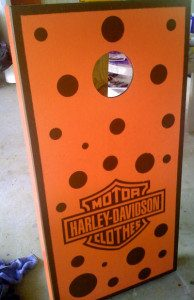Orange wooden cornhole board