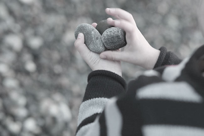 Kid holding several rocks in his hand and is about to toss them in a hole